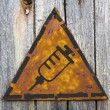 Foto Stock: Syringe Icon on Rusty Warning Sign.