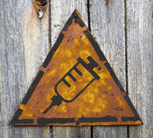 Syringe Icon on Rusty Warning Sign. — Stock Photo