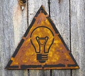 Light Bulb Icon on Rusty Warning Sign. — Stock Photo