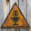 Microphone Icon on Rusty Warning Sign. — Stock Photo