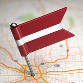 Pequeña bandera de letonia sobre un fondo de mapa. — Foto de Stock