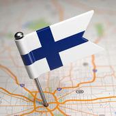 Pequeña bandera de finlandia en un fondo de mapa. — Foto de Stock