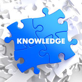 Knowledge Concept on Blue Puzzle. — Stock Photo