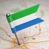 Serra leoa pequena bandeira sobre um fundo de mapa. — Foto Stock