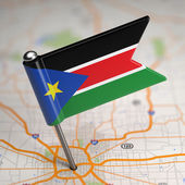 South Sudan Small Flag on a Map Background. — Stock Photo