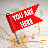 You Are Here - Small Flag on a Map Background. — Stock Photo