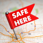 Safe Here - Small Flag on a Map Background with. — Foto Stock