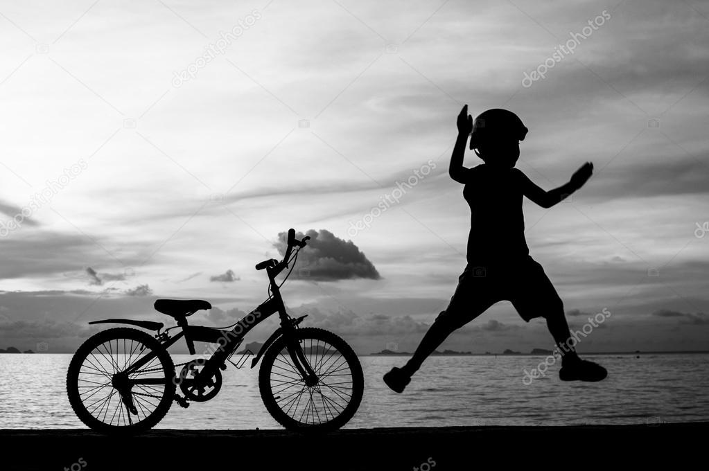 Silhouette of small boy on bike at dusk.  Stock Photo #14596929