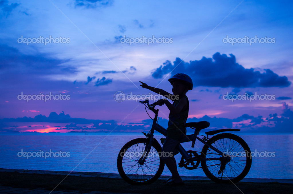 Silhouette of small boy on bike at dusk. — Stock Photo #14613883