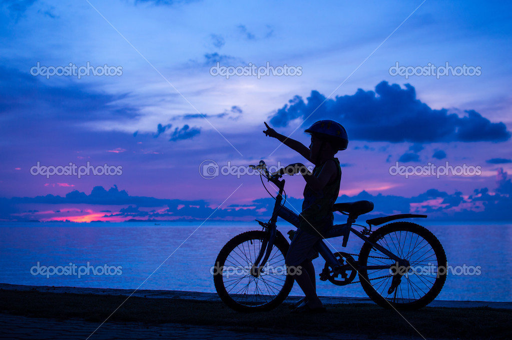 Silhouette of small boy on bike at dusk. — Stock Photo #14613927