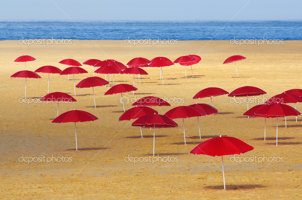 Many red umbrellas stuck in the sand of a beach in a summer morning — Stock Photo #13387197