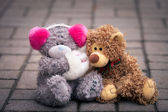 Couple of teddy bears sitting together on the street — Stock Photo