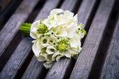 Beautiful wedding flowers bouquet on the dark wooden background — Stock Photo