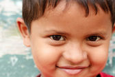 Closeup photo of a smiling and cute young asian/indian boy looki — Stock Photo
