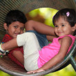 Cute young children(boy & girl) playing in tunnel on playground — Stock Photo