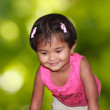 Beautiful young girl child happily playing in a park — Stock Photo