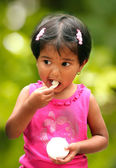 Beautiful young indian girl child enjoying ice cream in a park. — Stock Photo