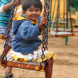 Beautiful & happy indian girl(child) playing on a swing in a pa — Stock Photo