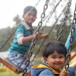 Cute young happy kids playing on swing sets in a park — Stock Photo