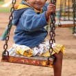 Cute young happy indian girl(kid) playing on a swing in a park — Stock Photo