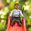 Pretty smiling indian boy(kid) on slider at a park — Stock Photo