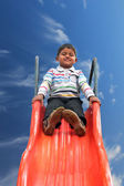 Beautiful smiling(happy) indian boy(kid) on slider in a summer d — Stock Photo
