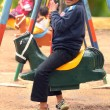 Happy young handsome boy(kid) playing on swing sets in a park — Foto de Stock