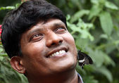 Handsome young Indian smiling with butterfly on face — Stock Photo