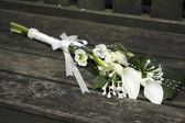 Wedding flowers on a bench — Stock Photo