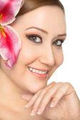 Leende kvinna lilja i hår — Stockfoto