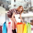 Happy shopping mall colorful bags surprised — Stock Photo