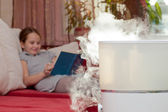 Girl reading book on the background of humidifier — Stock Photo