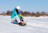 Mom and daughter rideing on sledge — Foto de Stock
