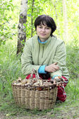 Girl in forest next to a basket of mushrooms — Stock Photo