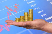 Business chart is made from golden coins on hand — Stock Photo