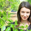 Young beautiful smiling through the branches of green tree — ストック写真