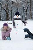 Beautiful girl near a snowman — Stock Photo