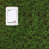 Electric power switch on a green grass background — Stock Photo