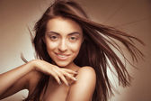 Attractive smiling woman with long hair on grey — Stock Photo