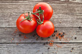 Dewy red tomatoes with pepper on old wooden table — Stock Photo