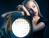 Sexy young woman with old floodlight — Stock Photo