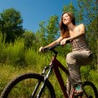 Pretty young woman with bicycle in a park smiling — Stock Photo