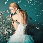 Постер, плакат: Bride in wedding dress behind bush with flowers