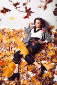 Brunette woman portrait in lying autumn leaves — Stock Photo