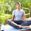 Young man doing yoga (lotus pose) in the park — Stock Photo