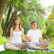 Young man and woman doing yoga in garden — Stock Photo
