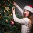 Happy woman decorating a christmas tree — Stock Photo