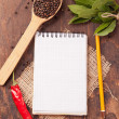 Spices in spoons, notebook on wood background — Stock Photo