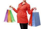 Pregnant woman holding shopping bags isolated — Stock Photo