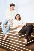 Couple at home sitting on stairs. Pregnancy — Stockfoto
